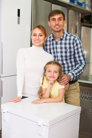 household appliance: portrait of  smiling family gladly shopping in household appliance store