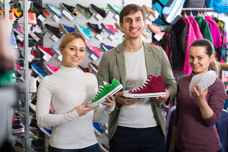 three persons: Three persons demonstrating shoes in the sport shop Stock Photo