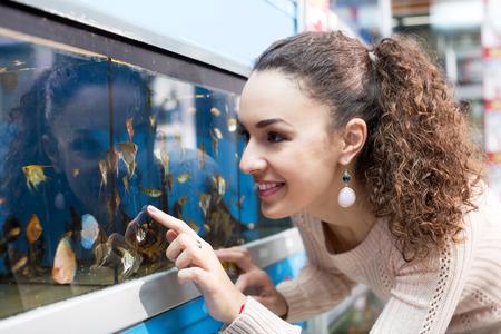 aquarian: Positive young girl selecting aquarium fish in pet shop