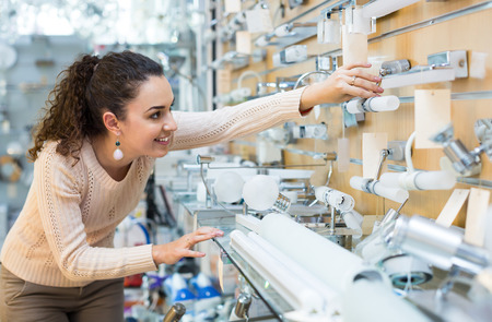 interior lighting: Girl selecting lighting units for interior in household store Stock Photo