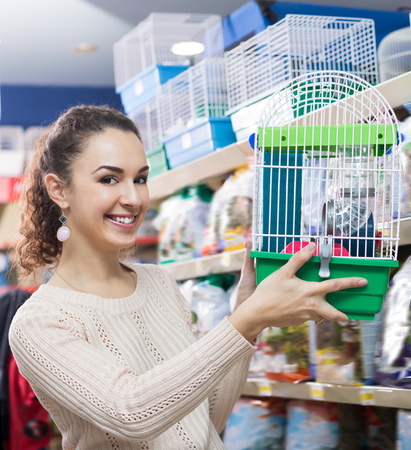 russian hamster: Young woman selecting birdcage for parrot in zoo store