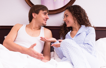 preparing food: Handsome young husband and smiling brunette wife talking in bed