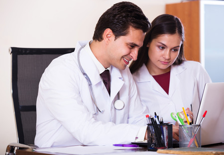 physiotherapists: Intern asking advice from medical tutor at clinic reception Stock Photo