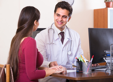 therapeutist: Portrait of patient and smiling therapeutist at desk in modern clinic Stock Photo