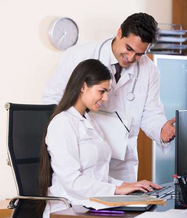 physiotherapists: Two spanish professional doctors brainstorming and sharing information in clinic Stock Photo