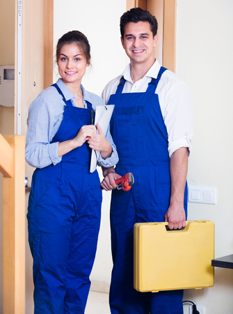tooling: Happy  indian handyman and female assistant in uniform with tooling