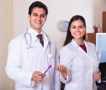 Portrait of two smiling therapeutists with stethoscope in private clinic
