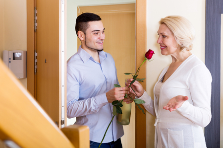 mismatch: Smiling son with gifts visiting elderly mother at her place Stock Photo