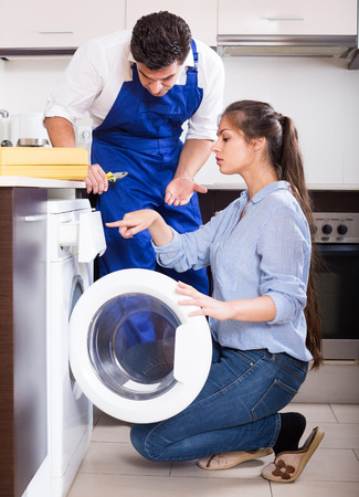mach: Young housewife and repairman near washing machine in domestic interior