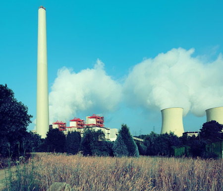cooling towers: plant with chimney and cooling towers in sunny summer day