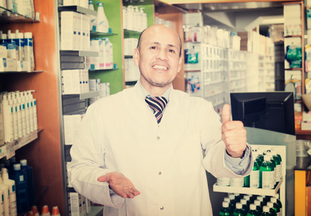 farmacy: Portrait of male pharmacist working in modern farmacy and smiling