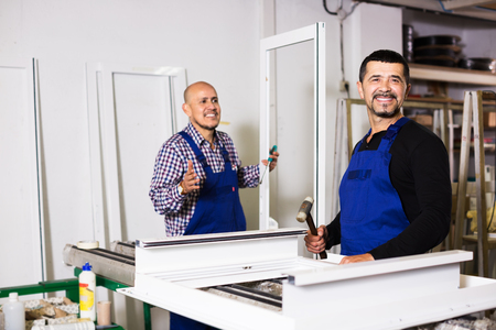 coverall: Two male labours in coverall working in PVC shop and smiling Stock Photo