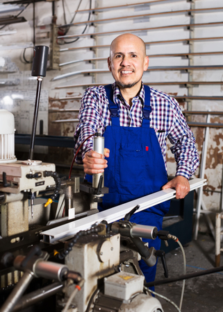 toolroom: Smiling labour working on lathe machine at factory