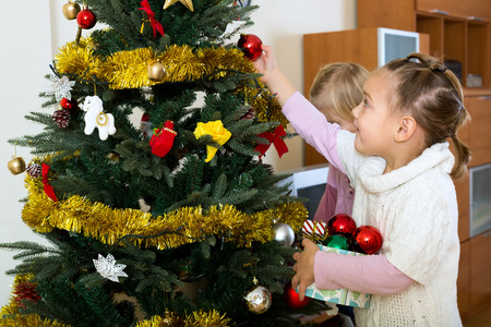 decorate: Happy children decorate fir for Christmas and New Year Eve