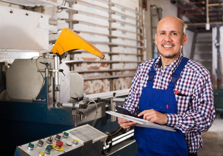 toolroom: middle age workman at professional lathe in plant