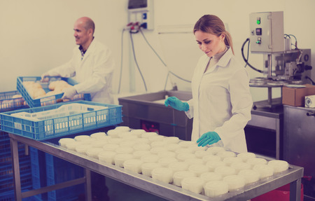 white coats: two  specialists in white coats at cottage cheese production process  on dairy factory . Focus on woman Stock Photo