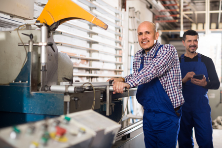 toolroom: Two smiling workmen in overalls near cutter - lathe machine at factory Stock Photo