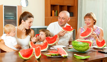 three generations: Happy three generations family eating watermelon  over  table at home interior Stock Photo