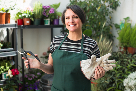horticultural: cheerful woman florist holding horticultural tools indoors Stock Photo