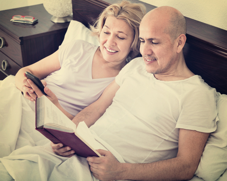 socialising: Mature boyfriend and girlfriend lying in bed socialising with mobile phones Stock Photo