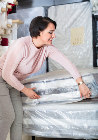 matress: Portrait of happy mature woman with matress in textile store Stock Photo