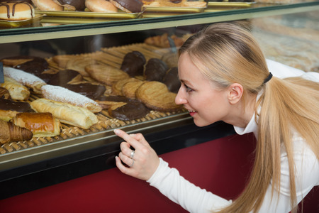 gladly: Young happy girl gladly selecting pastry in cafeteria store window