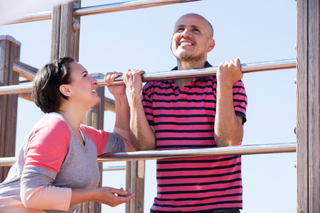 wall bars: Elderly happy man and woman standing together close to wall bars and smiling