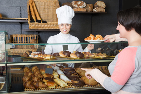 gladly: Happy cook gladly selling pastry to a customer in the cafeteria