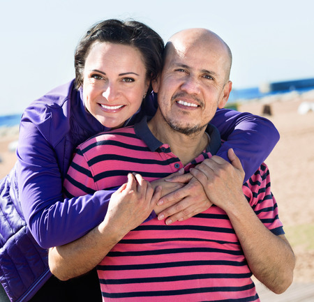 2 50: Positive smiling mature couple gladly hugging each other and enjoying the beach