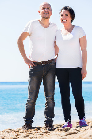 gladly: Pleasant positive smiling mature couple gladly hugging each other and enjoying the beach Stock Photo