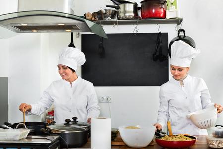 diligente: Glad diligentes mujeres chefs amigables que prepara el alimento en cocina del restaurante Foto de archivo