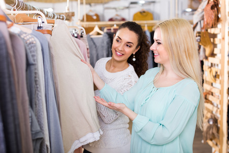 garments: Two smiling female friends selecting basic garments at the store