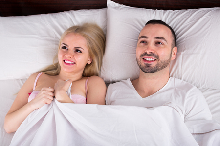 orgasm: Young man and girlfriend lounging in bed after making love