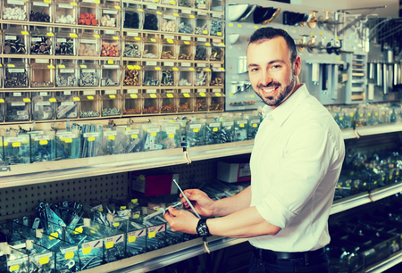 dowel: Happy adult man picking plastic dowel from stall in household shop Stock Photo