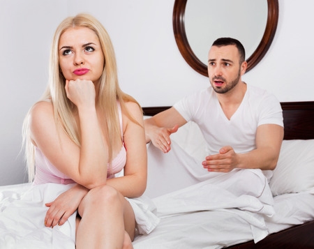 complaining: Cheerless beautiful woman turned away from man complaining in bed