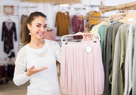 Cheerful smiling female customer buying new skirt at the store Stock Photo