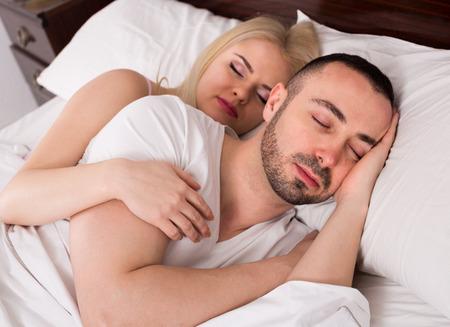 gente durmiendo: Los jóvenes que duermen juntos en la cama abrazando