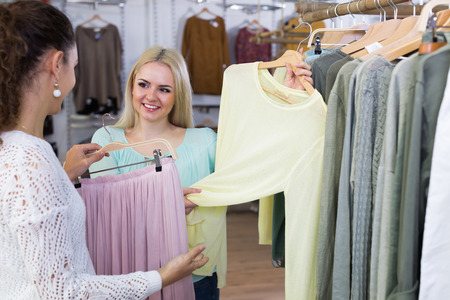 Excited young women choosing pullover and skirt at the apparel store