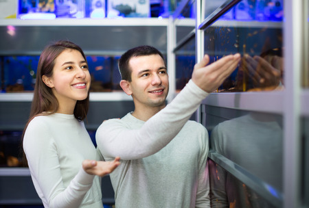 petshop: Portrait of happy excited young couple watching tropical fish in petshop Stock Photo