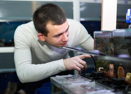 petshop: Portrait of european man selecting tropical fish in petshop Stock Photo