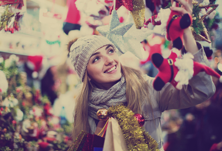 overspending: Happy glad cheerful girl choosing Christmas decoration at market in night time