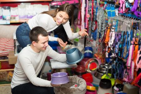petshop: Portrait of young spanish couple purchasing pet bowls in petshop