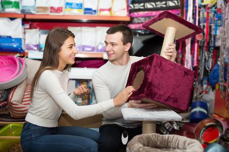 petshop: Portrait of happy american couple purchasing pet kennels in petshop