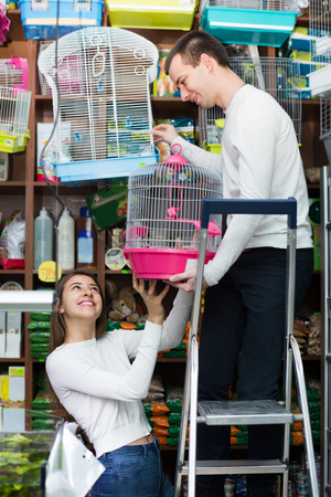 19's: Young couple of ordinary customers buying cage for bird in shop and smiling
