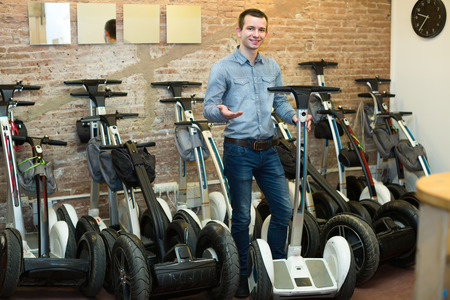 rental agency: Friendly smiling male consultant in front of segways at rental agency Stock Photo