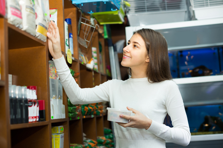 pet store: Positive young brunette carefully choosing dry food in pet store Stock Photo