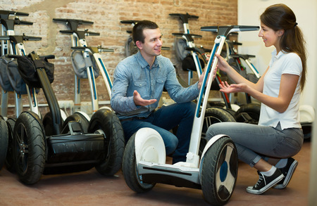 rental agency: Kindly male employee helping ordinary girl to select segway at rental agency