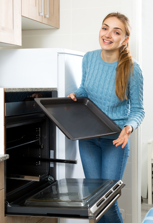 18's: Beautiful woman placing roasting tray in kitchen oven and smiling