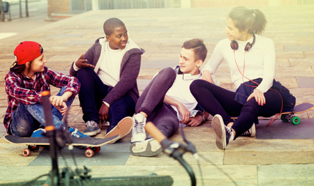 blabbing: Group of teens chatting near bikes  in sunny day outdoor