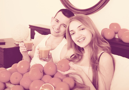Pleasant smiling couple with ripe oranges and freshly squeezed juice Stock Photo